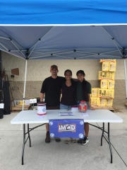 Josh and Rolette Warner and their oldest daughter, Leilani, 17, work at a fundraiser for the non-profit organization they co-founded, In Memory of Diesel. They help pet owners in need of food and other services for their pets.