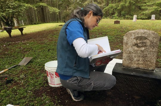 Jen Taylor flips through a binder that lists the graves in Bethel Cemetery as she, son Will, husband Brian and Mick Hersey help restore the gravestone of Juleyan Williams, at right, in the cemetery on Friday, May 22, 2020.