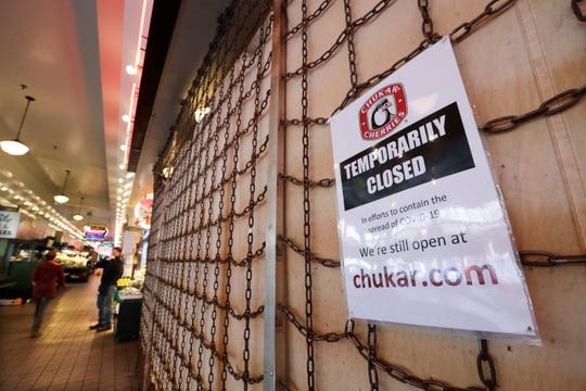 A sign explains the closure of a shop in the Pike Place Market in Seattle. As the coronavirus outbreak has caused record number of people to seek unemployment benefits Washington state officials said Thursday that impostors have used the stolen information of tens of thousands of people to receive hundreds of millions of dollars in unemployment benefits.