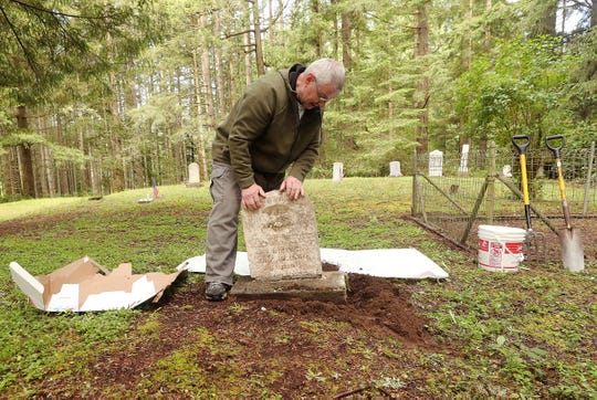 Mick Hersey sets the broken headstone of Juleyan Williams on its base at the Bethel Cemetery in Port Orchard on Friday, May 22, 2020. The broken stone was found at the Olalla cemetery and brought back to its rightful place through the research of Jen Taylor.