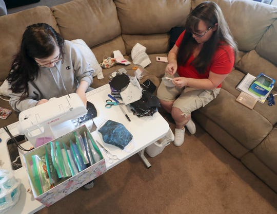 Brittany Singer and her mother Gina sew face masks on the couch of their Central Kitsap home on Thursday, May 21, 2020.