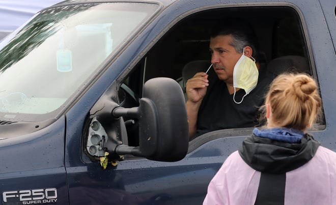 Donovan Ashworth swabs his nostrils while taking part in the Port Gamble S'Klallam Tribe's drive-thru COVID-19 testing in the parking lot of The Point Casino & Hotel on Thursday, May 21, 2020.