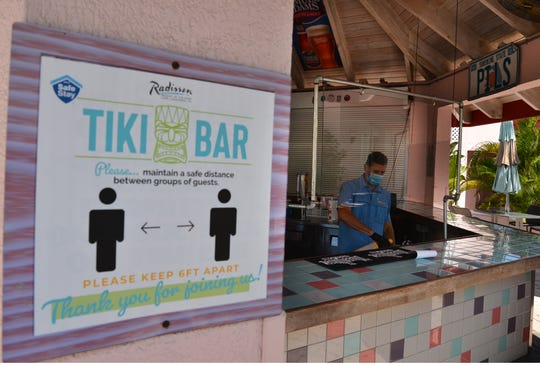 At the Radisson Tiki Bar in Cape Canaveral, there are social distancing rules posted and a sheet of Plexiglas between the bartender and customers.