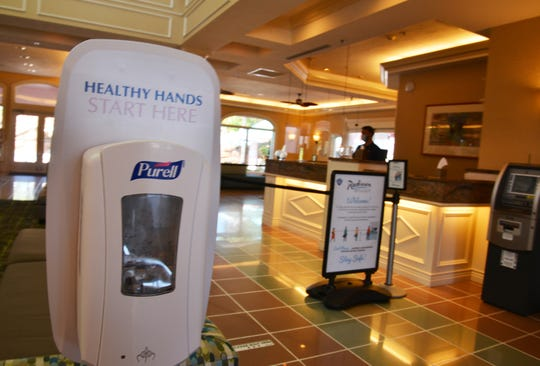 Among the first things that greet guests in the lobby of the Radisson Resort at the Port in Cape Canaveral are hand sanitizer, distancing markers on the floor, stanchions keeping customers back from the desk and Plexiglas protection for the front desk.