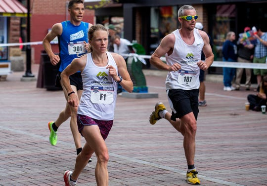 Eventual winner Kasie Enman, left, and her husband Eli run down Church Street during the People's United Bank Vermont City Marathon & Relay in Burlington on Sunday, May 24, 2015.