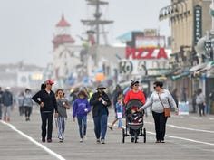 Ocean City boardwalk fans take a stroll in the rain to kickoff Memorial Dayweekend on Friday, May 22, 2020.