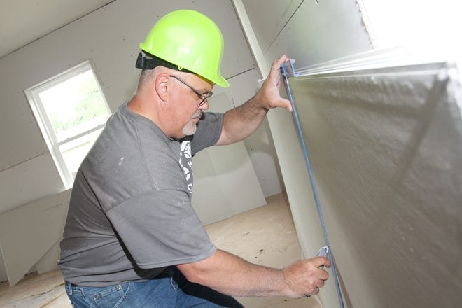 Tim Brown of D&P Communications cuts drywall Thursday during a home renovation for Lenawee County Habitat for Humanity in Adrian.