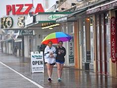 Crowds stroll a wet boardwalk on Friday during the start of Memorial Dayweekend in Ocean City, N.J.