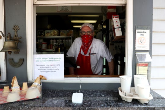 Chip Adkins, owner of Piper's Cafe, stands for a portrait in the pick-up window, Friday, May 22, 2020, in Covington, Ky. Kentucky Gov. Andy Beshear ordered restaurants and bars to stop indoor services on March 16 to stop the spread of the novel coronavirus, and on Friday, restaurants were able to open indoor dining rooms, contingent on following strict social distancing and sanitation measures.