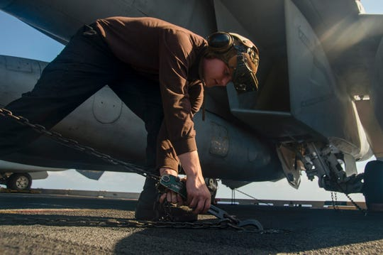 Aviation Machinist Mate 3rd Class David Bauer, from Cincinnati, attaches a chain to a pad-eye on the flight deck of the Nimitz-class aircraft carrier USS Harry S. Truman (CVN 75) in the Atlantic Ocean May 16, 2020.