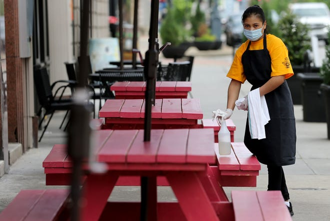 """An associate cleans off outdoor tables shortly after opening, Friday, May 22, 2020, at Agave & Rye in Covington, Ky. One staff member has also been dubbed the """"Sanitation Ninja"""" whose sole job is to constantly clean the restaurant. Kentucky Gov. Andy Beshear ordered restaurants and bars to stop indoor services on March 16 to stop the spread of the novel coronavirus, and on Friday, restaurants were able to open indoor dining rooms, contingent on following strict social distancing and sanitation measures."""