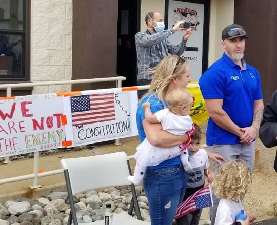 Kyle Newell, right, with his wife and children at the re-opening of his gym in Hillsborough on Monday, May 18.