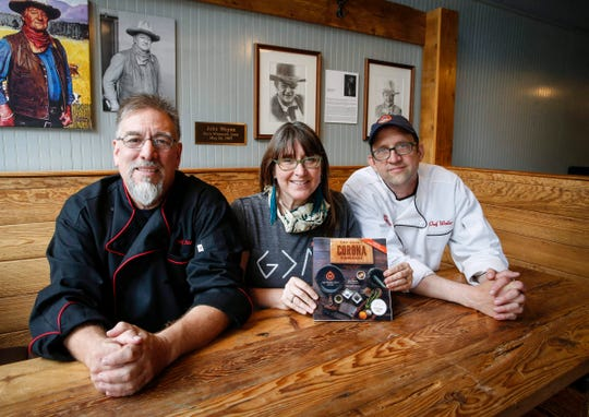 Northside Cafe owners Scott Valencia, left, and Michele Jahncke and head chef Walter Jahncke pose for a portrait at the Northside Cafe in Winterset on Friday, May 22, 2020, with their new cookbook, The Novel Corona Cookbook.
