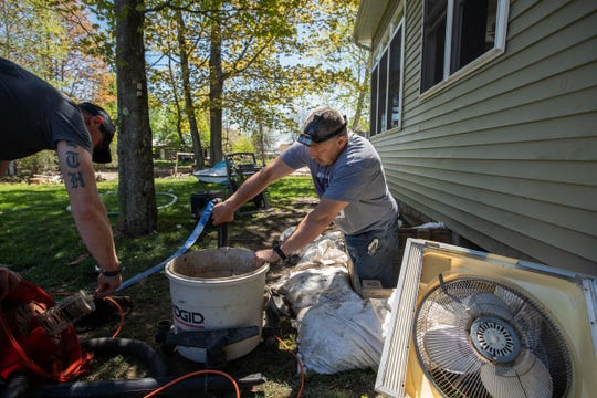 Terry Holsinger (left) of Bay City helps Mike Desco get a shopvac ready to help clear water from the crawl space underneath his home in Beaverton on Thursday, May 21, 2020.
