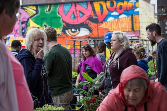 Shoppers mull over choices during Flower Day at Eastern Market in Detroit on May 20, 2018.