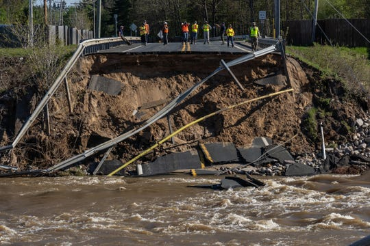 Workers look over the damage of a washed-out bridge on M-30 above Wixom Lake on May 21, 2020, after the Edenville Dam failed from heavy rains that flooded the area