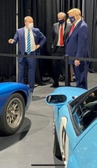 Bill Ford Jr., executive chairman of Ford Motor Co., points to a collection of Ford GT vehicles while talking with President Donald Trump during his visit to the Rawsonville plant in Ypsilanti on May 21, 2020. Mark Meadows, White House chief of staff, is standing in the middle.