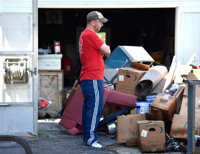 Shaun Johnson, of Dewitt, looks down as he says he doesn't want to cry as he and family members remove items out the basement of his flooded family cottage.