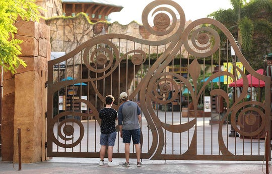 FILE - In this Thursday, May 14, 2020, file photo, guests peer through the closed gate to Universal's Islands of Adventure beside Universal CityWalk, in Orlando, Fla.