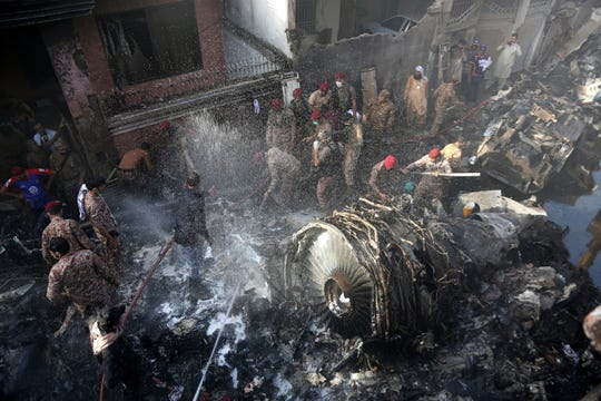 Volunteers look for survivors of a plane that crashed in residential area of Karachi, Pakistan. An aviation official says a passenger plane belonging to state-run Pakistan International Airlines carrying more than 100 passengers and crew has crashed near the southern port city of Karachi.