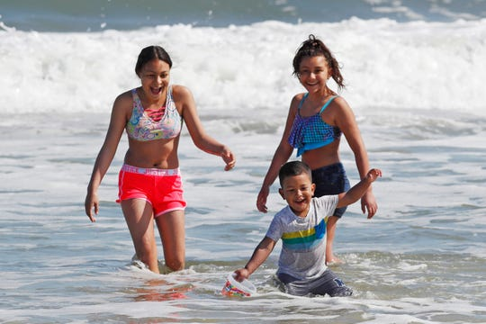 In spite of signs prohibiting swimming due to the absence of lifeguards, youngsters play in the surf, Thursday, May 21, 2020, at Jones Beach in Wantagh, N.Y., amid the coronavirus pandemic.