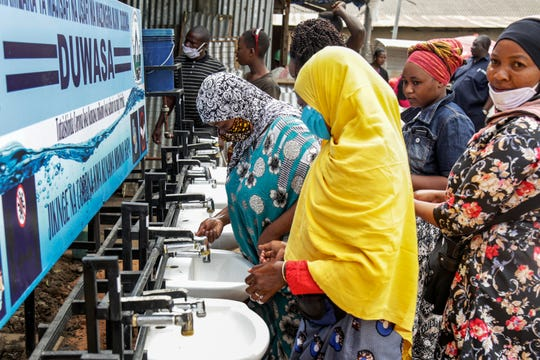In this photo taken Monday, May 18, 2020, people use a hand-washing station installed for members of the public entering a market in Dodoma, Tanzania.