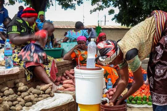 In this photo taken Monday, March 30, 2020, traders sit by the vegetables they are selling at a street market in Dodoma, Tanzania.
