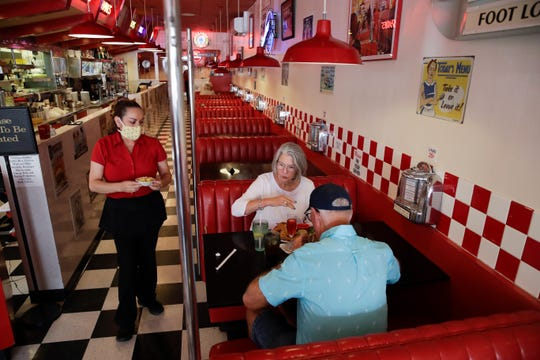 Lynn Tanner, center, and her husband Ryan, bottom right, are served lunch at Busy Bee Cafe Thursday, in Ventura, Calif.