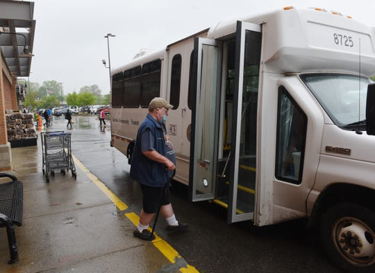 A senior citizen boards the Livonia Community Transit bus after his shopping trip at Kroger Supermarket in Livonia, May 22, 2020.
