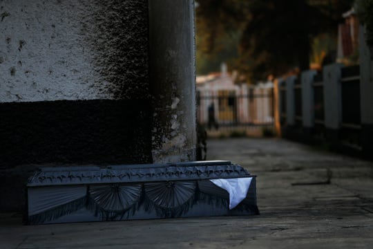 An empty coffin that once held the body of a COVID-19 victim sits outside the crematorium at the San Nicolas Tolentino Pantheon as workers cremate bodies in the Iztapalapa area of Mexico City.