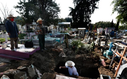 Cemetery musician Victor Dzib Cima, 70, plays his accordion as he waits for clients while cemetery workers remove coffins from gravesites that belonged to families who stopped paying rent at the San Nicolas Tolentino Pantheon, where he has worked for tips for 22 years, in the Iztapalapa area of Mexico City on Friday.