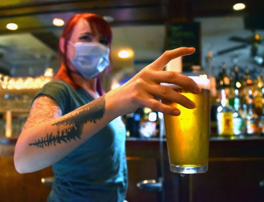 Bartender Lawren Grunow, 23, holds a cold beer shortly after Brady's Bar in downtown Traverse City opened their doors for the first time since mid-March at 12:01 a.m. Friday.
