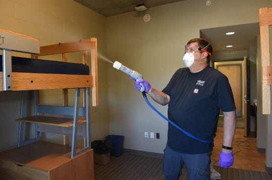 Mike Zinser disinfects a room in a Oakland University residence hall in preparation for the return of students.