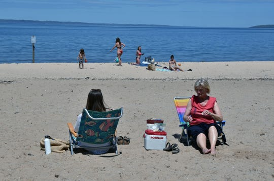 Sherry Oyer, right, enjoys a day on the beach at Bryant Park with her granddaughter Marilyn Oyer on Friday, May 22, 2020. Living in Traverse City, the two practiced social distancing from a few other beach goers and relaxed along the shore of Grand Traverse Bay.