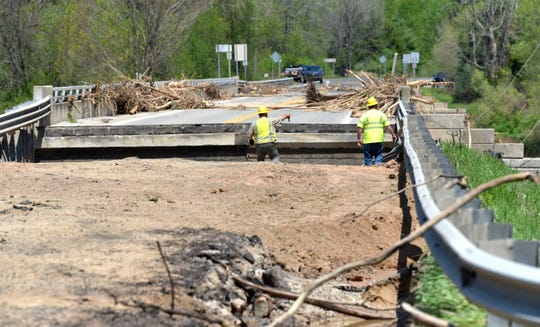 Utility workers survey the M-30 washed out bridge over the Tittabawassee River in Edenville.