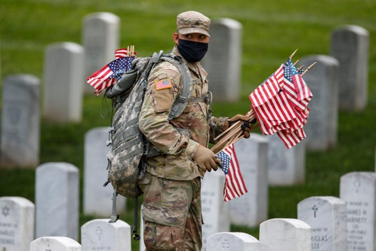 """Wearing a face mask, a member of the 3rd U.S. Infantry Regiment also known as The Old Guard, places flags in front of each headstone for """"Flags-In"""" at Arlington National Cemetery in Arlington, Va., Thursday, May 21, 2020, to honor the Nation's fallen military heroes ahead of Memorial Day.\"""