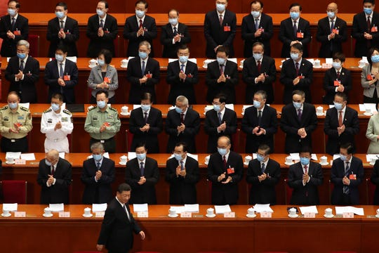 Delegates applaud as Chinese President Xi Jinping arrives for the opening session of China's National People's Congress (NPC) at the Great Hall of the People in Beijing, Friday, May 22, 2020.
