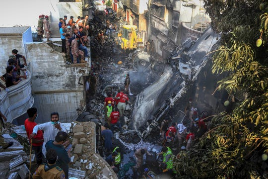 Volunteers look for survivors of a plane that crashed in a residential area of Karachi, Pakistan.