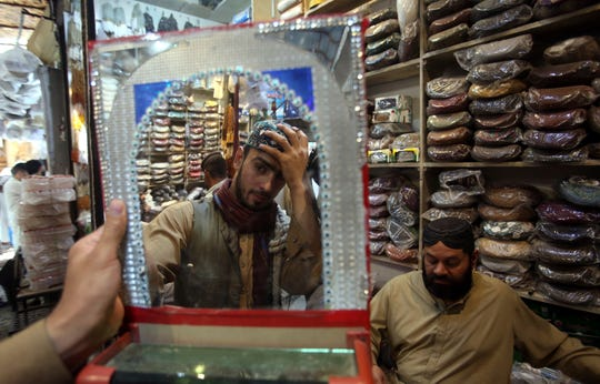 A customer tries a traditional cap for the upcoming Eid al-Fitr holiday that marks the end of the Muslim holy fasting month of Ramadan after the government relaxed a weeks-long lockdown that was enforced to help curb the spread of the coronavirus, in Peshawar, Pakistan, Friday May 22, 2020. (AP Photo/Muhammad Sajjad)