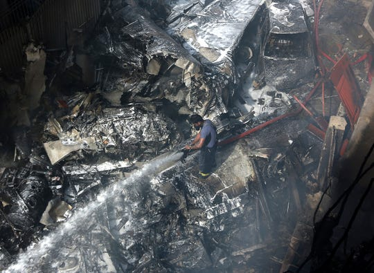 A firefighter tries to put out fire caused by plane crash in Karachi, Pakistan, Friday.