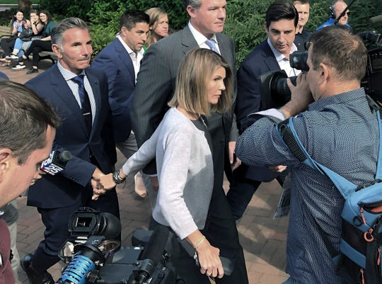 In this Aug. 27, 2019, file photo, Lori Loughlin departs federal court with her husband, clothing designer Mossimo Giannulli, left, in Boston, after a hearing in a nationwide college admissions bribery scandal.