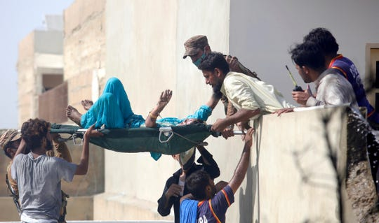 Volunteers carry an injured person at the site of a plane crash in Karachi, Pakistan, Friday.