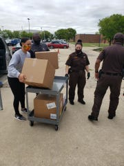 Detroit Council President Pro Tem Mary Sheffield and Wayne County Sheriff's Office Chief of Jails and Court Operations Robert Dunlap help unload personal protective equipment, secured by Sheffield from General Motors, in front of the Wayne County Jail Thursday.