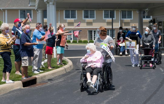Helen Miller, center, Mary Jo Scott, right, and Naomi Spurling, back, parade in front of family and friends during a celebration Friday afternoon, May 22, 2020. The three women are the first to graduate from Hamilton Pointe's COVID-19 wing after four weeks of being cared for in isolation, a result of testing positive for the novel coronavirus.