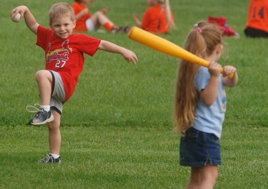 As two of their cousins play baseball on the fields surrounding them, Jack Patterson, 3, of Newburgh, winds-up a pitch while playing with his cousin Kaelyn Johnston 5, of Evansville at the Evansville Youth Baseball east fields in Evansville on Tuesday, May 9, 2006.