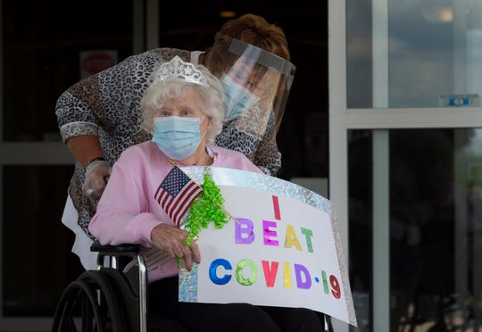 Helen Miller exits the main entrance of Hamilton Pointe during a celebration parade Friday afternoon, May 22, 2020. Miller, 90, was among the first to graduate from Hamilton Pointe's COVID-19 wing after four weeks of being cared for in isolation, a result of testing positive for the novel coronavirus.