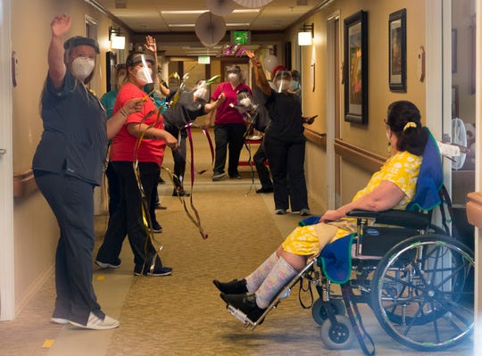 Hamilton Pointe nursing home staff wave down the hallway during a celebration parade for three residents that recovered from COVID-19 Friday afternoon, May 22, 2020.