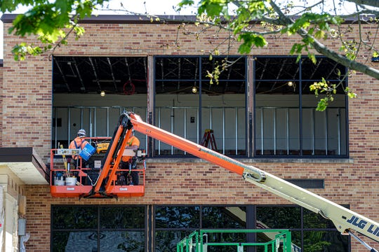 Two construction workers work on Waters Elementary School Wednesday, May 20, 2020 in Fond du Lac, Wis as part of a $98 million referendum project to make improvements to four Fond du Lac Schools.