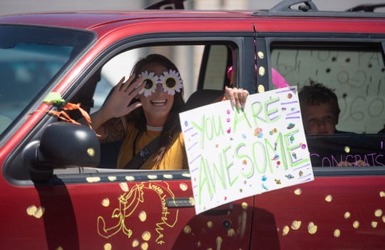 A woman waves and holds a sign during a drive-by parade celebration for graduates and those transitioning out of the Cooper Home, a transitional learning program, in Fort Collins, Colo. on Friday, May 22, 2020.