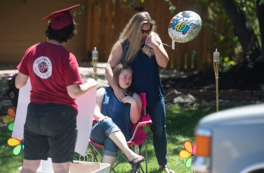 Amanda MacMillan reacts as she stands beside her graduating daughter Kaeda MacMillan during a drive-by parade for graduates and those transitioning out of the Cooper Home in Fort Collins, Colo. on Friday, May 22, 2020.